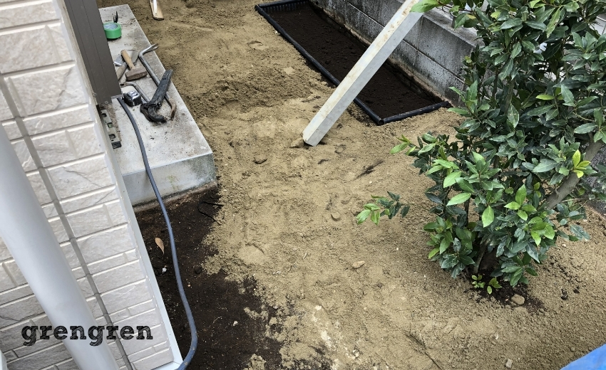 人工芝の施工のために下地として山砂を撒いた日陰の庭