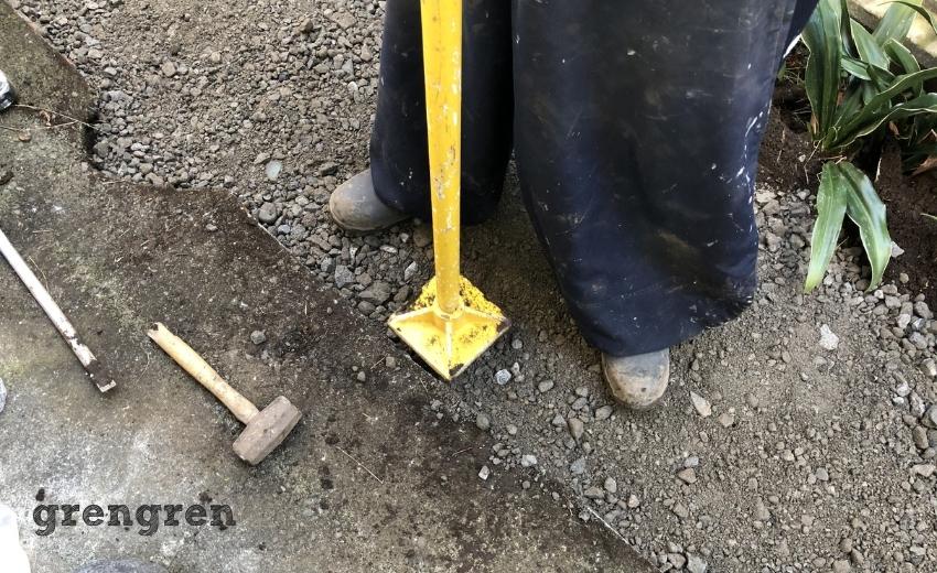自然石を設置する前に路盤材をタンパで固める職人