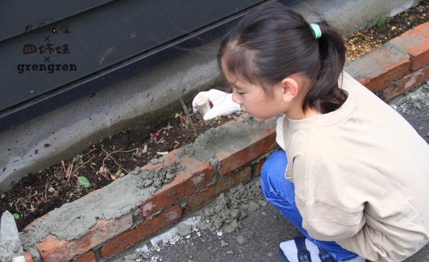 レンガ花壇をつくるためにモルタルをのせてくれる小さな職人さんたち