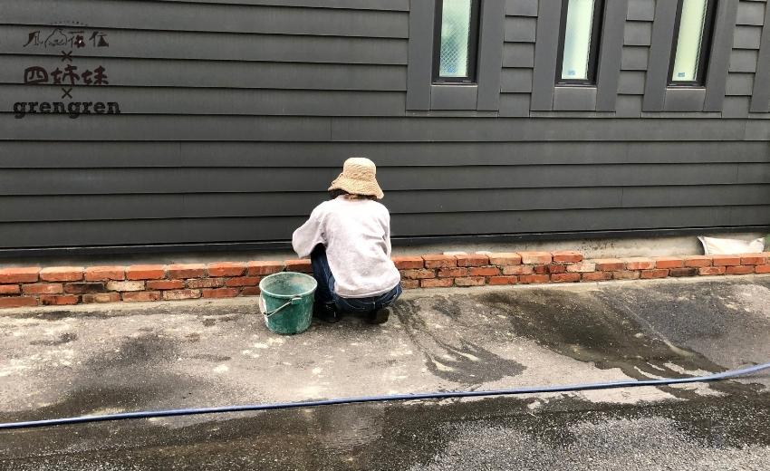 レンガの表面を綺麗な水でセメントをふき取る作業をする造園会社ぐりんぐりんの職人