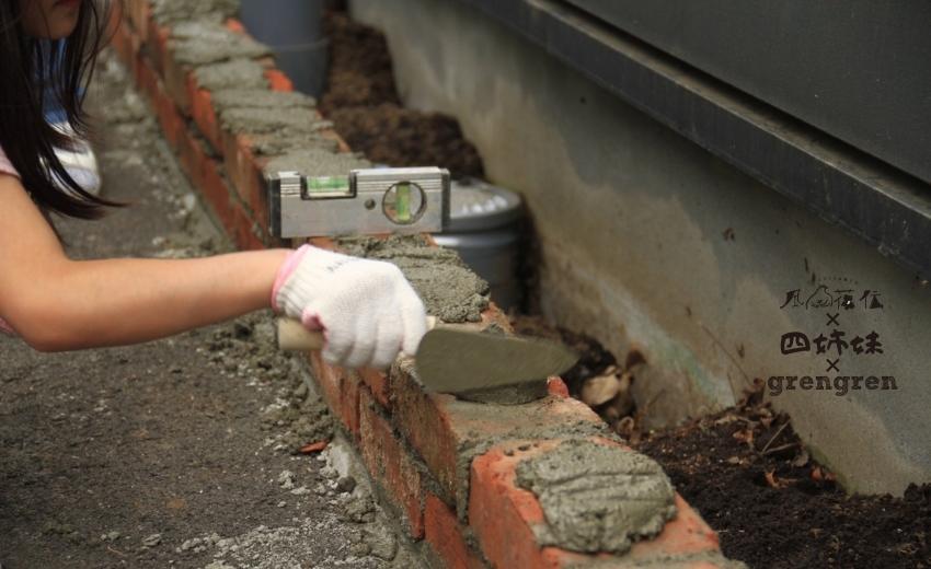レンガ花壇を作るためレンガの上にモルタルをのせる小さな職人さん