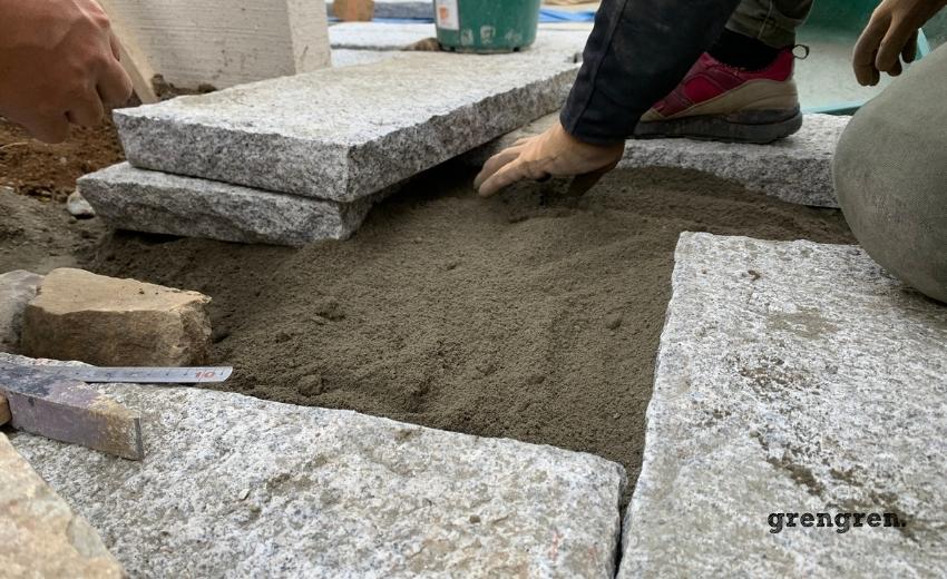 セメントが混ざった砂を下地に石材を設置する