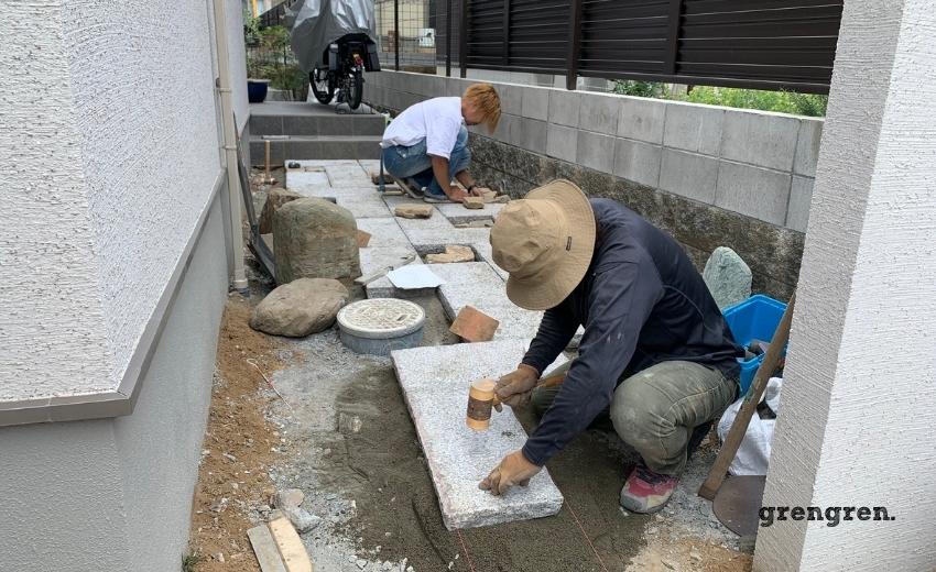 一枚づつ高さや方向性、角度を確認して石材を設置する職人さん